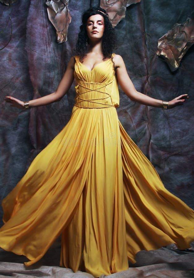 Brunettkvinna som bär den gula aftonklänningen royaltyfri fotografi