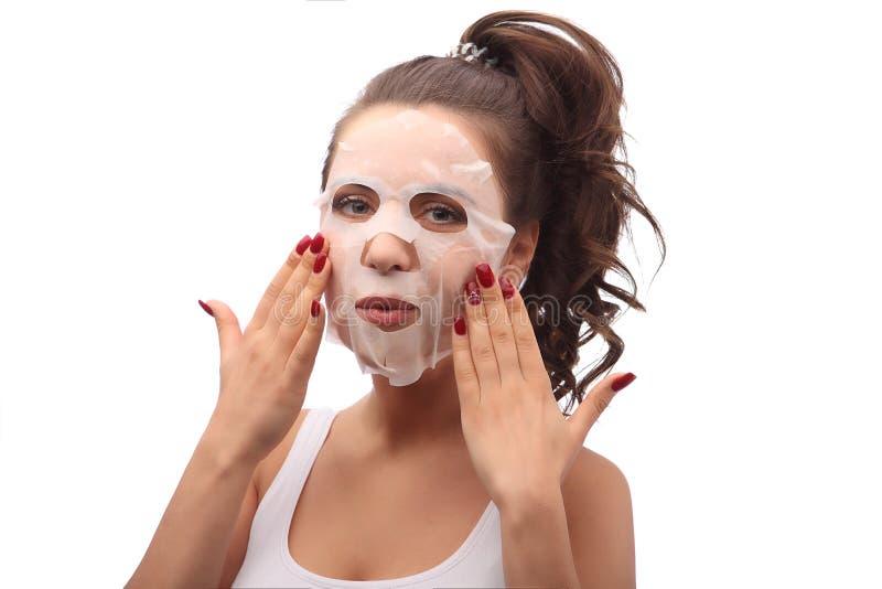 Brunettkvinna som gör det ansikts- maskeringsarket Skönhet och begrepp för hudomsorg Flicka som applicerar den ansikts- maskering royaltyfria bilder