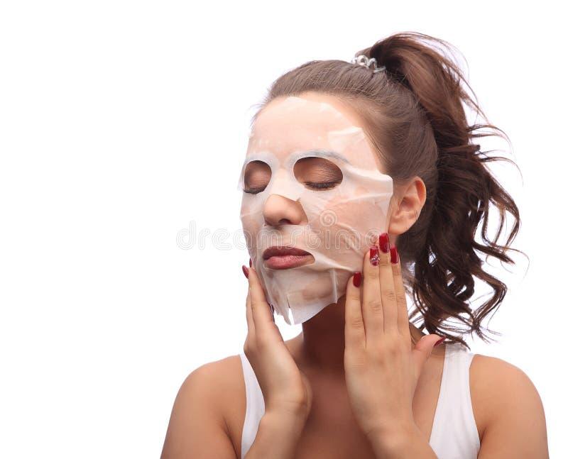 Brunettkvinna som gör det ansikts- maskeringsarket Skönhet och hudomsorg Flicka som applicerar den ansikts- maskeringen, fotografering för bildbyråer