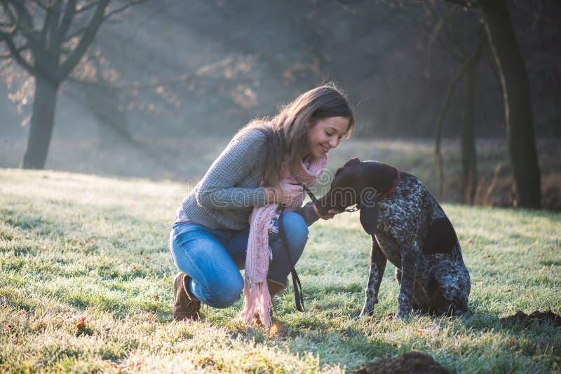 Brunettkvinna som poserar med hennes förtjusande tyska pekarehund arkivbild