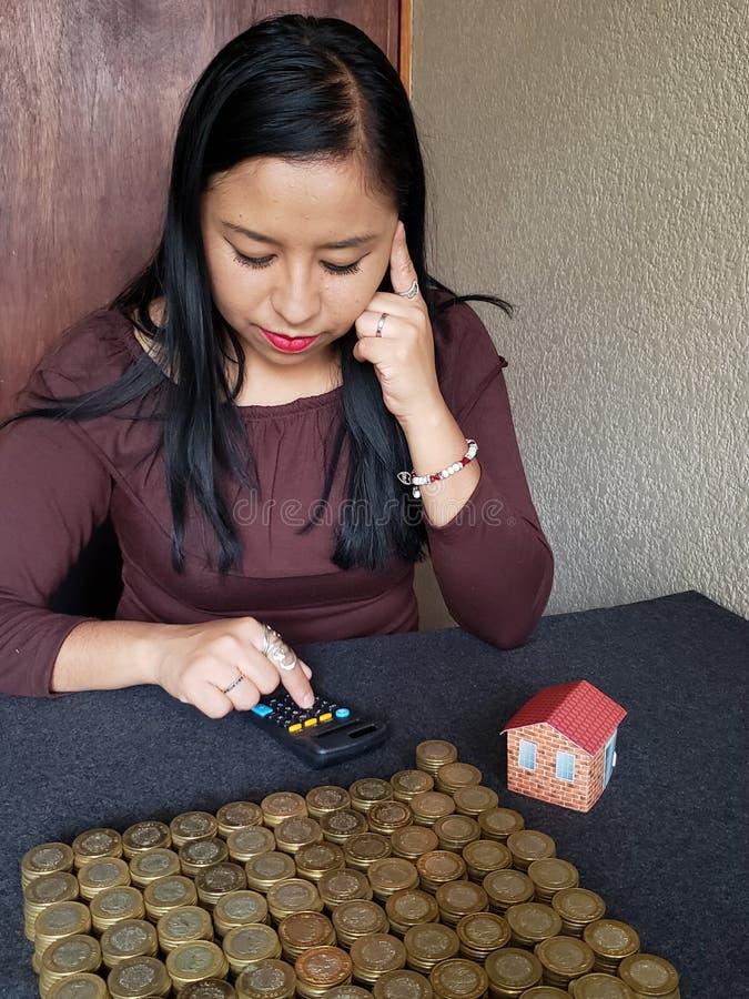Brunettkvinna som sparar mexicanska pengar för att investera i ett hem arkivfoto