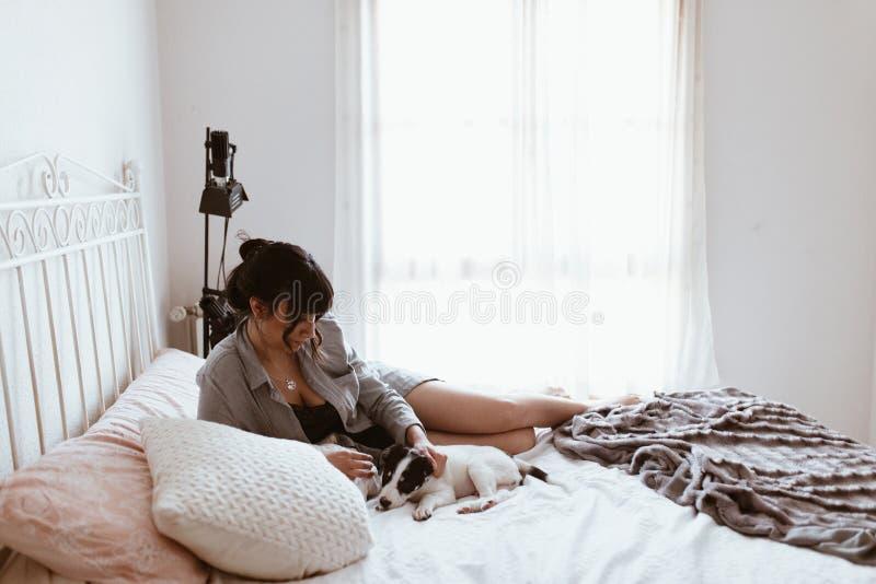 Brunettkvinna som spelar med valpen, medan ligga p? s?ng p? sovrummet royaltyfria bilder