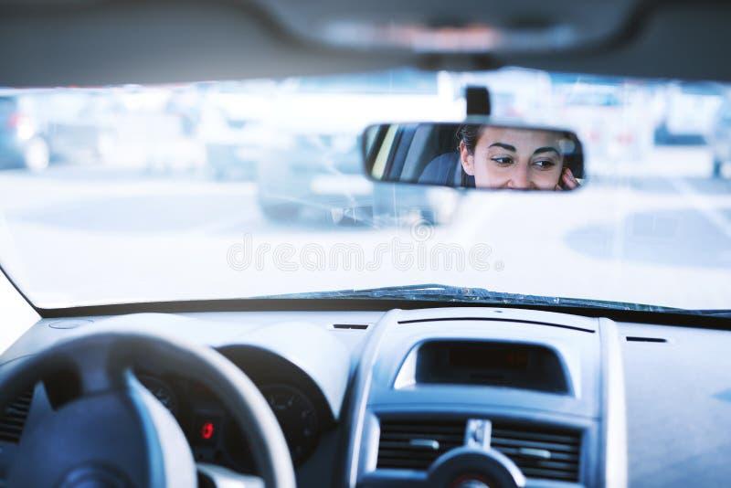 Brunettkvinna som talar på en mobiltelefon, medan köra en bil bakre sikt till och med backspegeln arkivbild