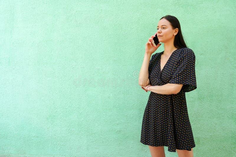 Brunettkvinna som talar vid smartphonen på grön bakgrund med kopieringsutrymme royaltyfri foto