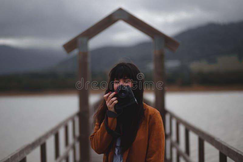 Brunettkvinnafotograf med det orange dikelaget p? en bro fotografering för bildbyråer