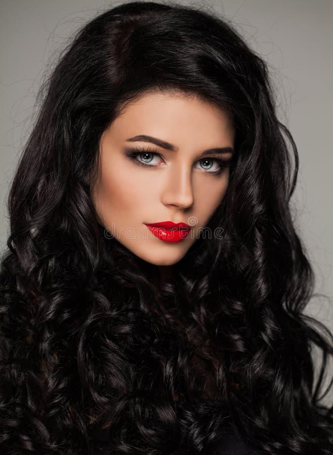 Brunettkvinnaframsida Elegant kvinnlig modell med den lockiga frisyren royaltyfri bild