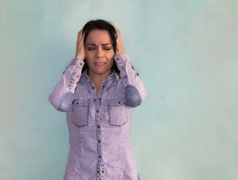 Brunettkvinnalidande från huvudvärk och migrän som är desperat med händer på hennes huvud arkivbild