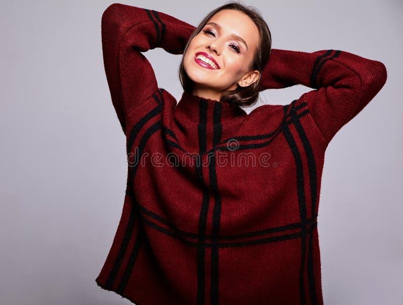 Brunettkvinnamodell i stilfull kläder som poserar i studio arkivfoto