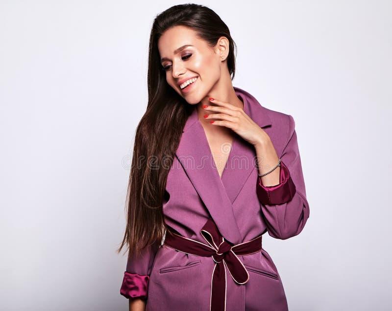 Brunettkvinnamodell i stilfull kläder som poserar i studio fotografering för bildbyråer