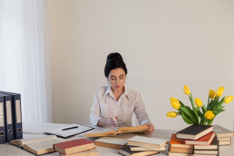 Brunettkvinnan i en affärsdräkt läser böcker i kontoret royaltyfria bilder