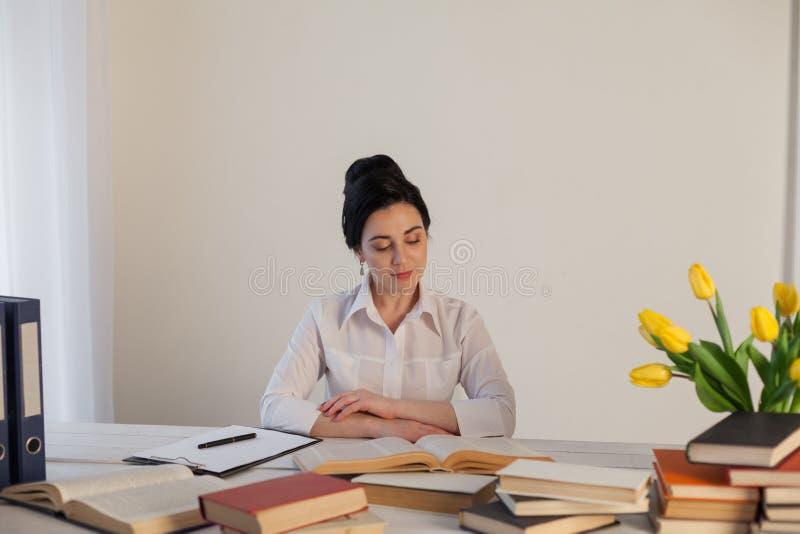 Brunettkvinnan i en affärsdräkt läser böcker i kontoret royaltyfri fotografi
