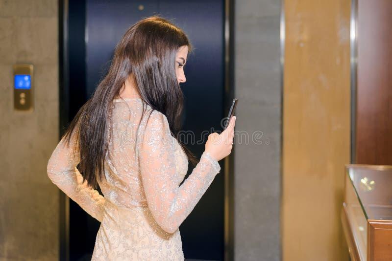 Brunettkvinnan i en aftonklänning rymmer smartphonen arkivbild