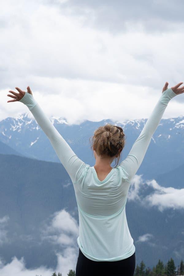 Brunettkvinnan med tillbaka att vända mot kameran, lyfter armar, medan tycka om bergsikten på den olympiska nationalparken i Wash arkivbilder