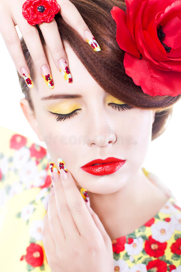 Brunettkvinnan med vallmoblomman i hennes hår, vallmocirkel och idérikt spikar, stängde ögon arkivfoto