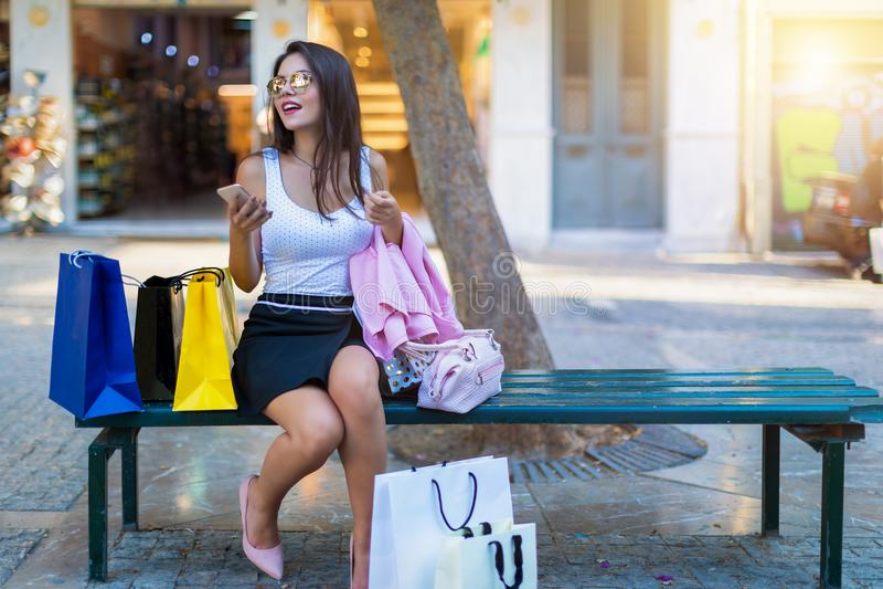 Brunettkvinnan sitter på en bänk som omges av shoppingpåsar royaltyfria bilder