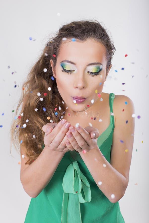 Brunettkvinnaslag bort konfettierna på hennes födelsedagparti fotografering för bildbyråer