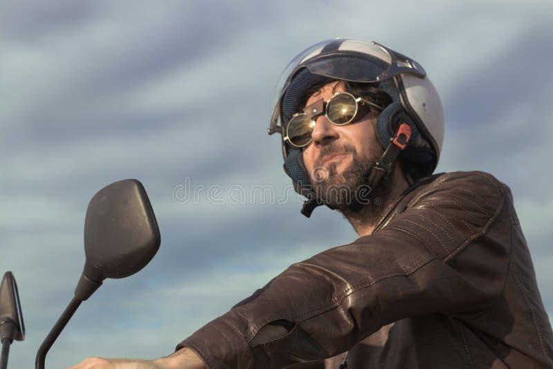 Brunettman med bruntläderomslaget på en moped arkivbilder
