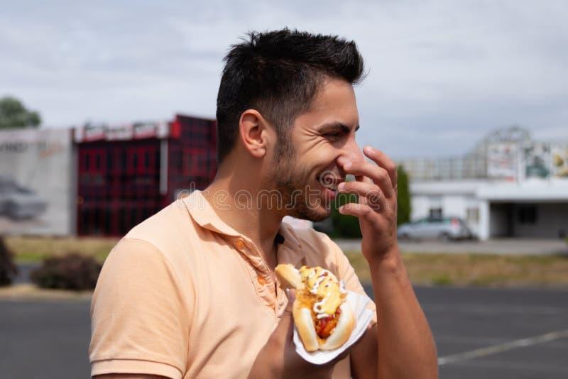 Brunettman som äter varmkorven i parkeringen arkivfoton