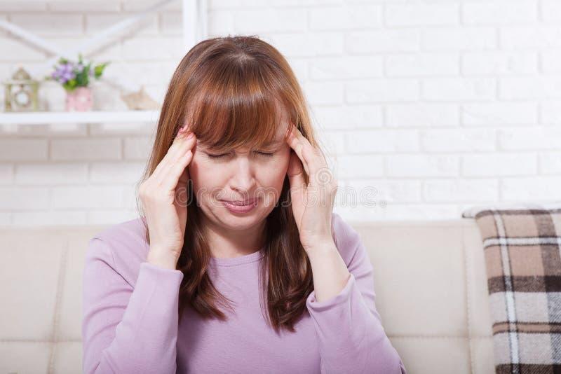 Brunettmitt åldrades kvinnan som har huvudvärk på hem- bakgrund Klimakterium och spänning Fördjupning Kopieringsutrymme och åtlöj royaltyfri fotografi
