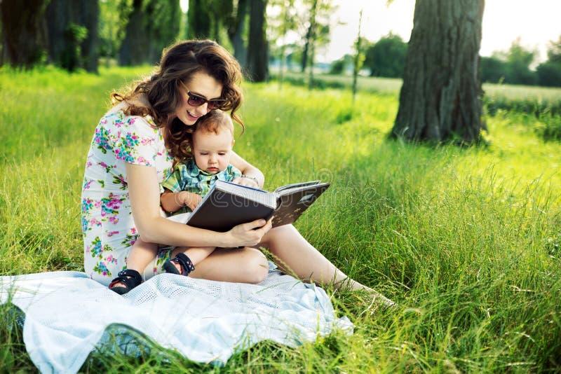Brunettmoder som läser en saga för hennes barn royaltyfria bilder