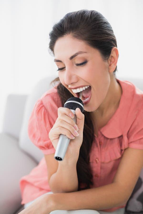 Brunettsammanträde på hennes soffa som sjunger in i mikrofonen royaltyfria foton