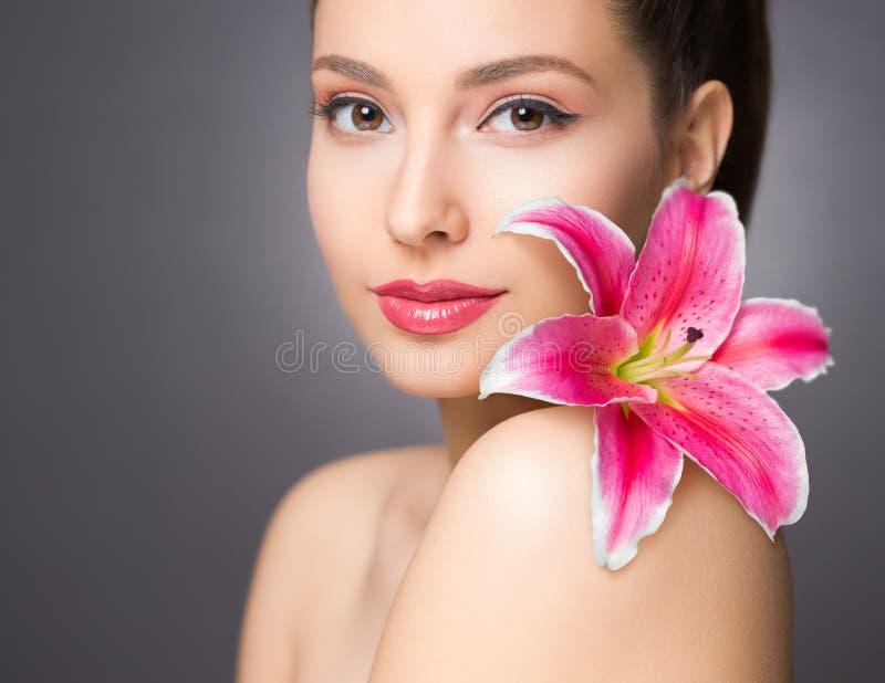 Brunettskönhet med den färgrika blomman royaltyfri fotografi