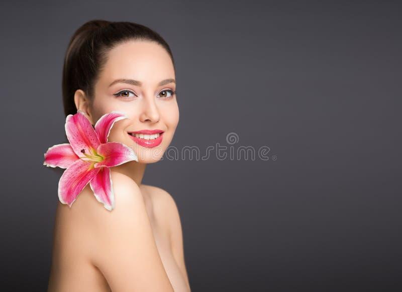 Brunettskönhet med den färgrika blomman royaltyfria bilder