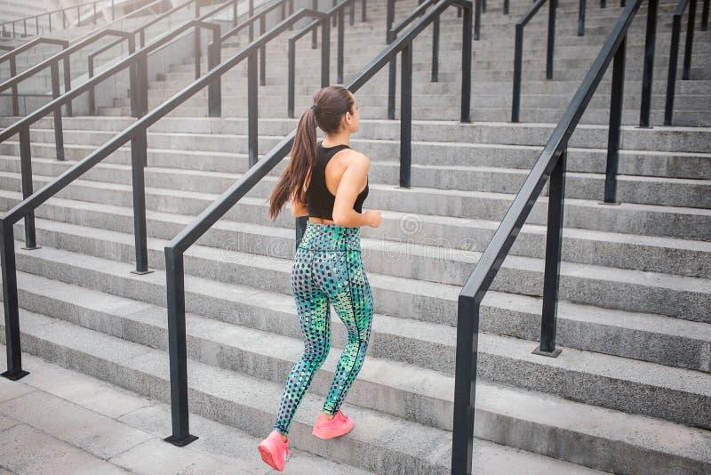 Brunn-byggt och format jogga för ung kvinna Han kör upp på trappa Flickan bär den bra sportlikformign Hennes flätade trådar för h royaltyfri bild