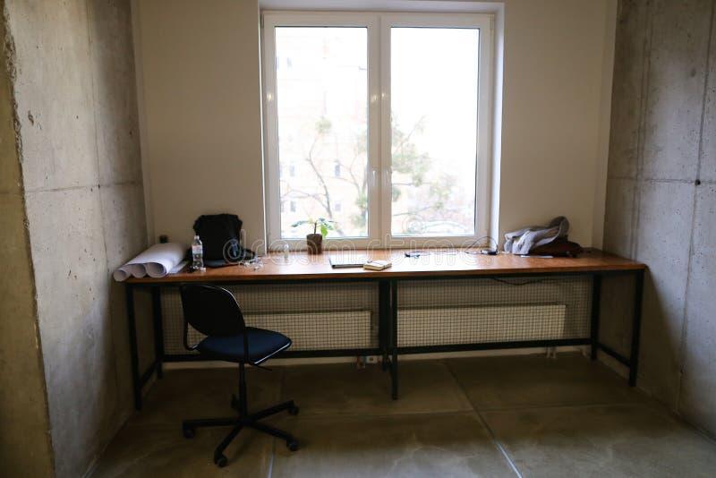 Brunn-utrustad arbetsplats med anordningar i ljust rum med vind arkivbild