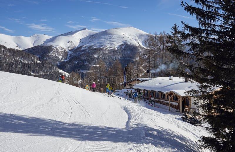 Brunnach ośrodek narciarski, St Oswald, Carinthia Austria, Styczeń, - 20, 2019: Kabina obok narciarskiego skłonu z narciarkami w  obraz stock
