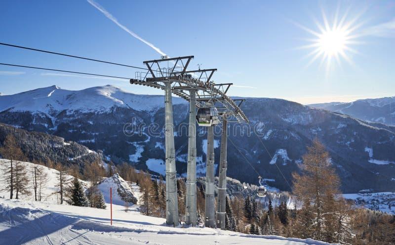 Brunnach Ski Resort, St Oswald, Carinthia, Österrike - Januari 20, 2019: Sikt på de sista pelarna av den Brunnach gondolöverkante arkivfoto
