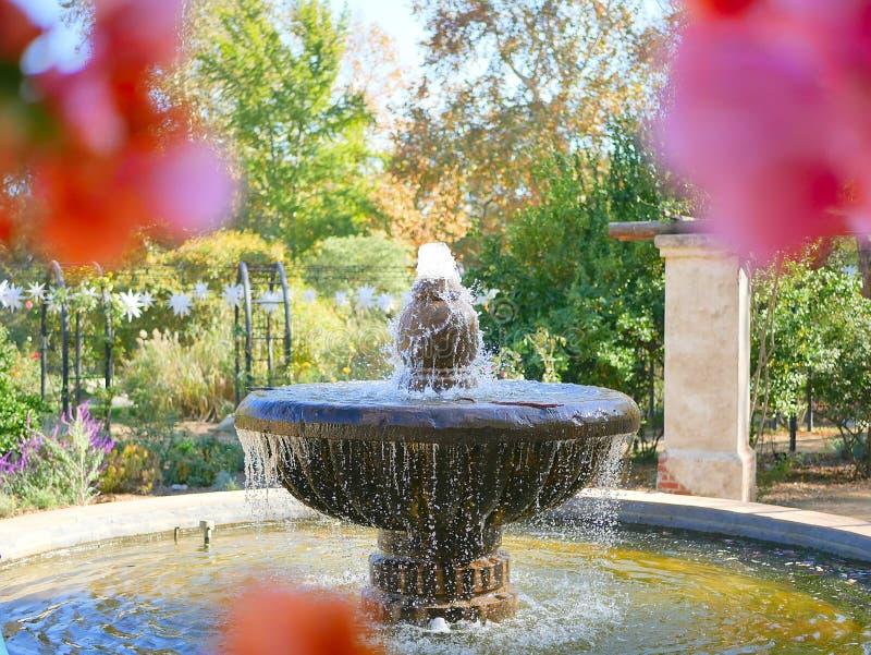 Brunnen mit rosa Blumen im Vordergrund lizenzfreie stockbilder