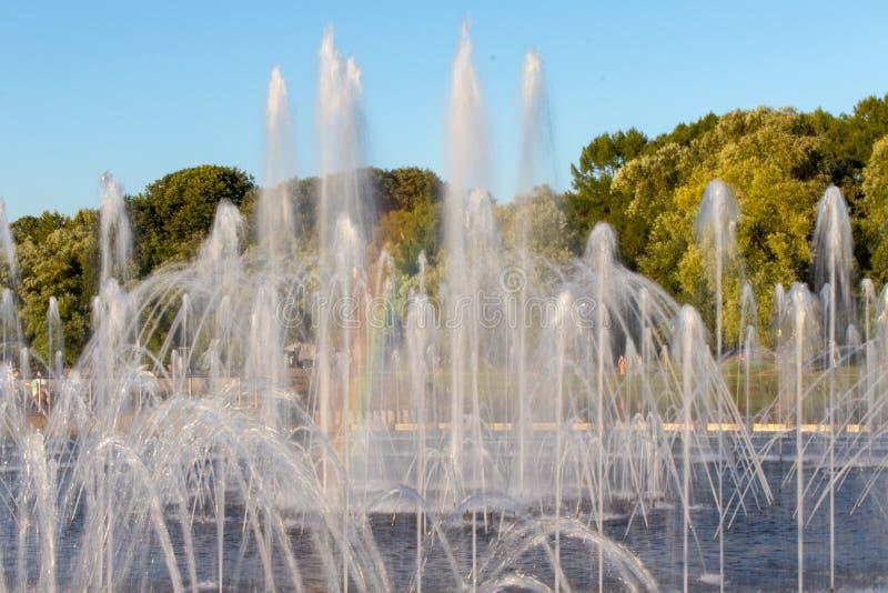 Brunnen mit Wasser, das herauf verschiedene Ströme spurtet Mehrfarbiger Regenbogen im Brunnen stockfotos