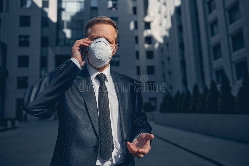 Brunnsborst i antivirala respiratorer som pratar på mobiltelefon utomhus fotografering för bildbyråer