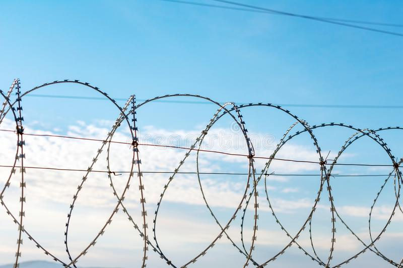 Bruno`s spiral against the blue sky. Barbed wire against a blue sky with feathery clouds. Close-up photo royalty free stock image