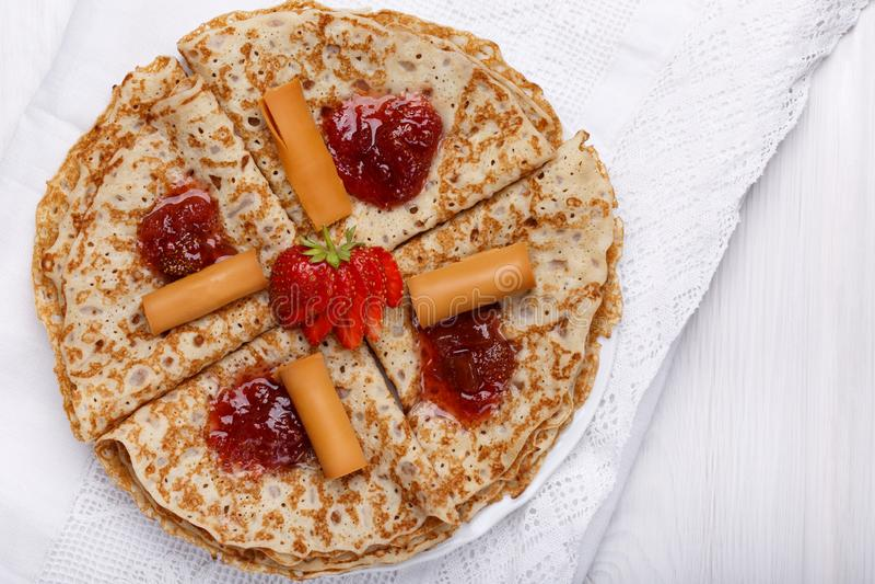 Brunost noruego en la tabla blanca Crepes hechas en casa con queso y mermelada de fresa marrones escandinavos foto de archivo libre de regalías