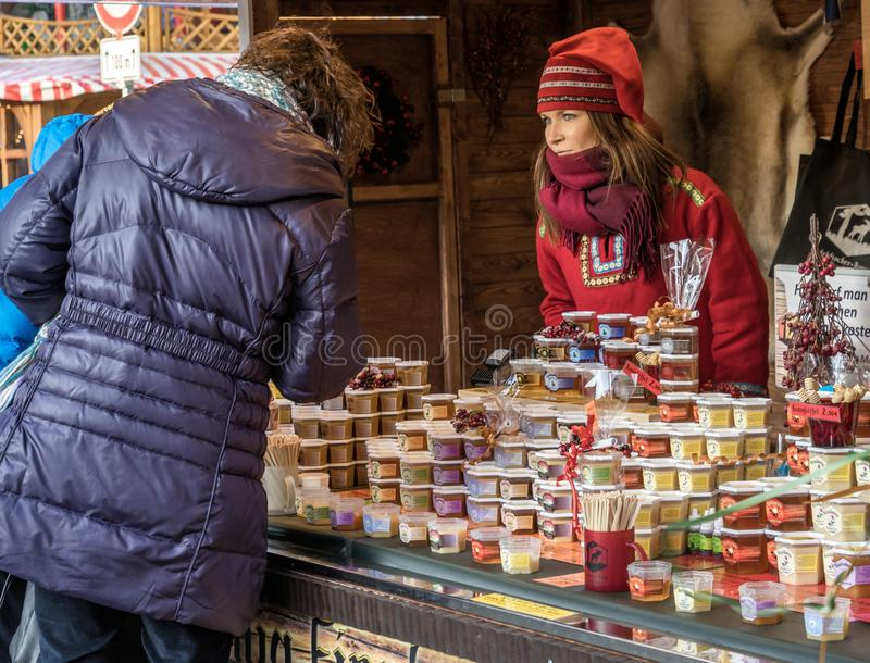 Brunswick, Lower Saxony, Germany, December 7th 2017: Booth with. Honey from Finland with a shop assistant in Finnish costume at the Christmas market in stock images