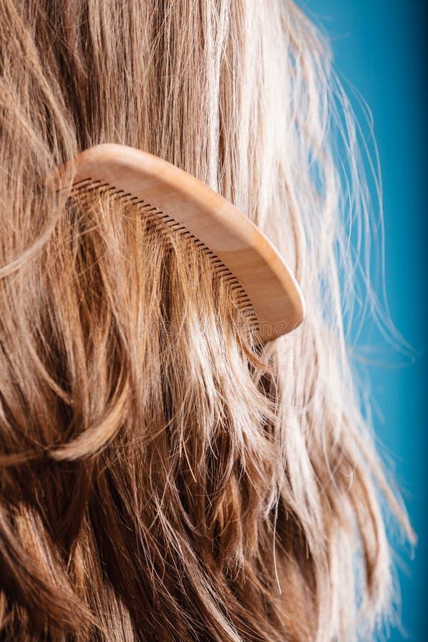 Brunt hår för raksträcka med trähårkamcloseupen royaltyfri foto