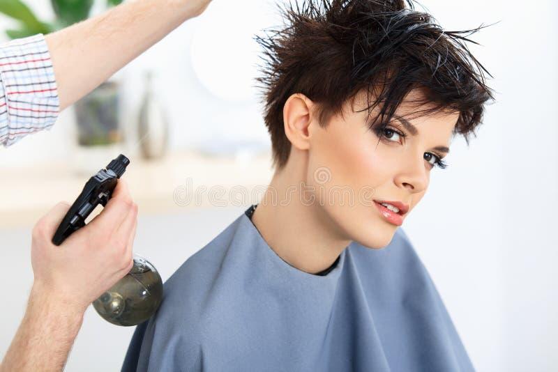 Brunt hår. Frisören som gör frisyren i hårsalong. arkivbild