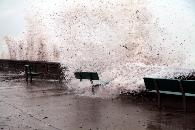 Brunt of Hurricane Irene. A seawall cannot hold back the wrath of Hurricane Irene. A bench on the other side of the wall get doused with sea water and seaweed stock image