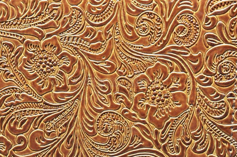 Brunt läder som utföra i relief med en blom- modell arkivfoton