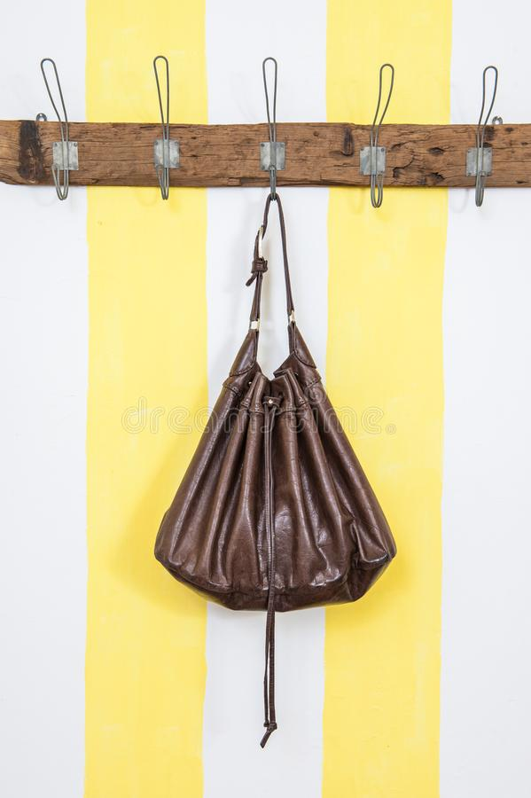 Brunt piskar handväskan på trägarderob arkivfoto