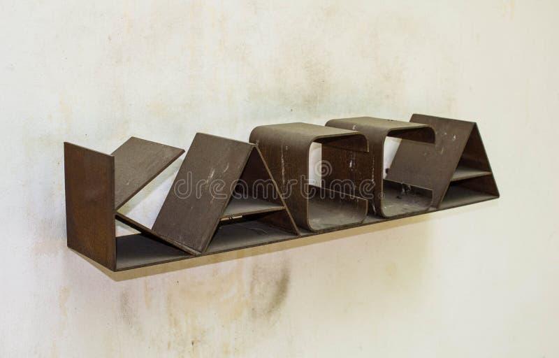 Brunt rostigt tecken på kassörskan på bakgrunden av ljusa väggar Kassa på väggen royaltyfri bild