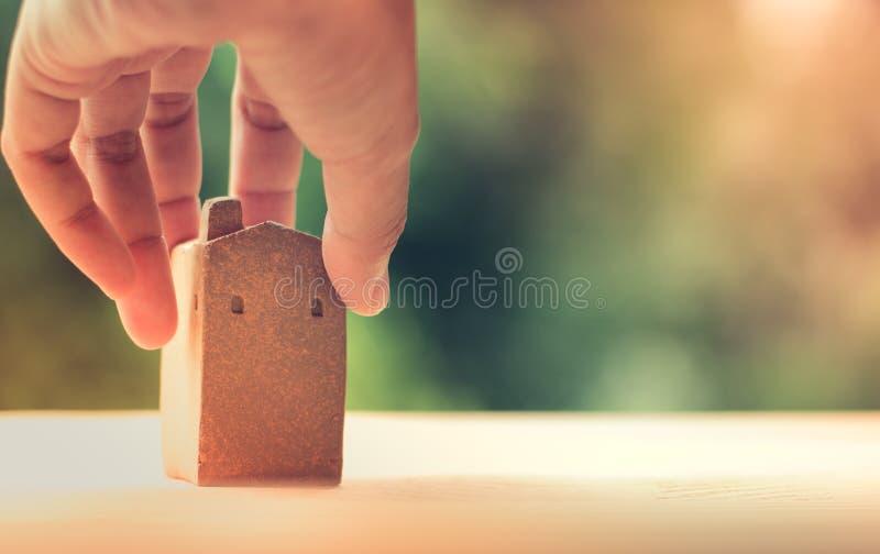 Brunthemmodell som göras från lera på träyttersida som rymmer av den vänstra handen, suddig grön bokeh som bakgrund, kopieringsut royaltyfri fotografi