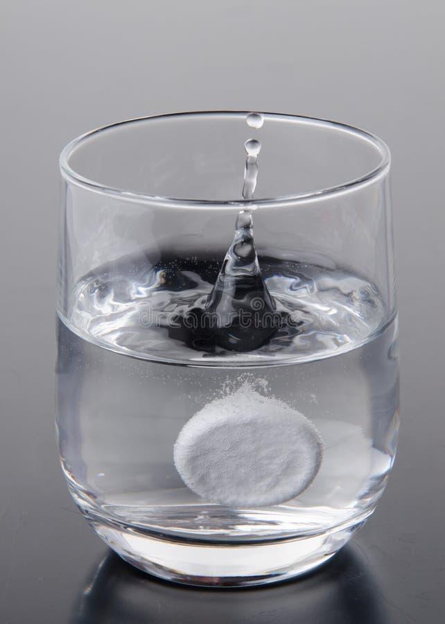 brusa fallande glass tabletvatten arkivbilder