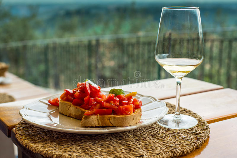 Bruschete alla Pomodore with ehite wine glass. Delicious toast with tomatoes on a plate with white wine glass. Low DOF, shot on a warm sunny afternoon in Tuscany stock photography