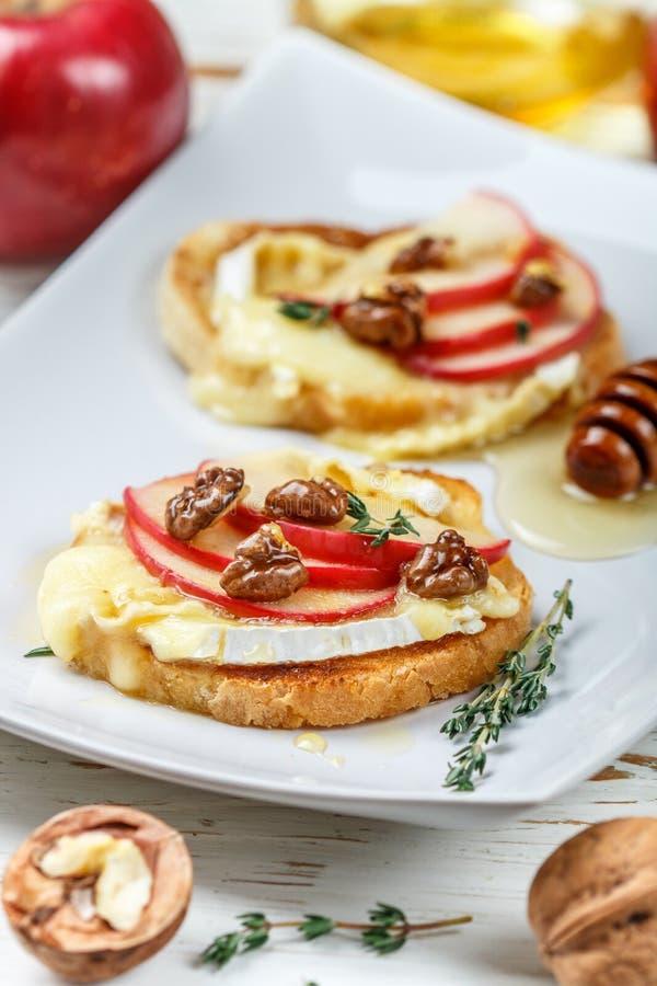 Bruschetta三明治用咸味干乳酪或软制乳酪乳酪、苹果、核桃、麝香草和蜂蜜 库存图片