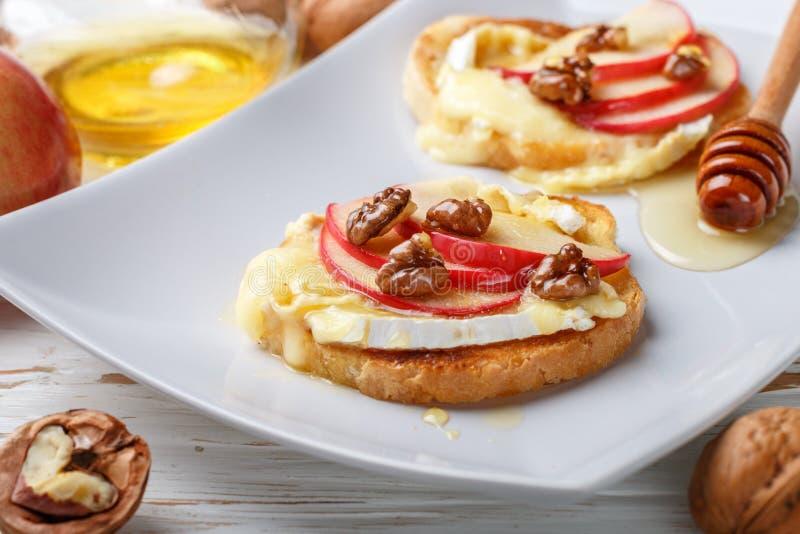 Bruschetta三明治用咸味干乳酪或软制乳酪乳酪、苹果、核桃和蜂蜜 库存照片