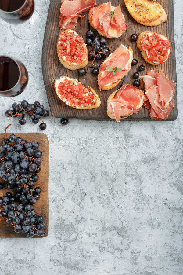 Bruschetta和三明治用火腿与两杯酒 免版税库存图片