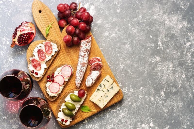 Bruschetta或地道传统西班牙塔帕纤维布、红葡萄酒和葡萄在灰色背景 看法从上面,平的位置 免版税库存照片